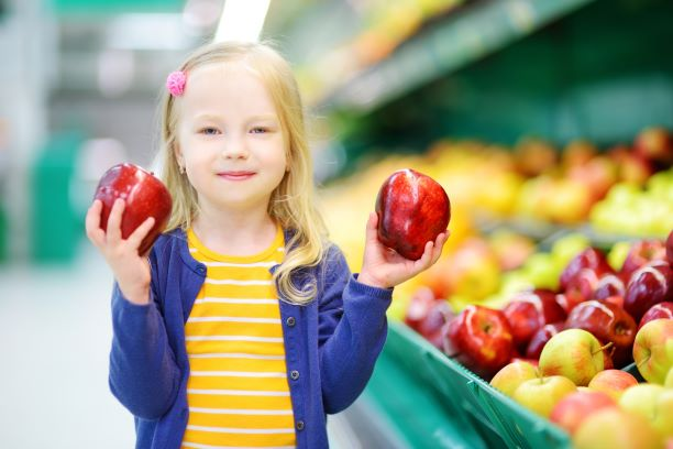 A young girl standing in the fruit section of a grocery store holding a red apple in each hand.