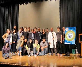 Scientists and students stand on a stage, smiling toward the camera.
