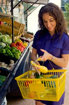 Photo of woman at grocery store holding a basket of vegetables