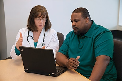 Photo of doctor with patient looking at computer