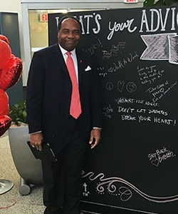 Photo of Dr. Griffen P. Rodgers standing next to chalk board where he composed the message 'Heart-felt advice - don't let diabetes break your heart!'