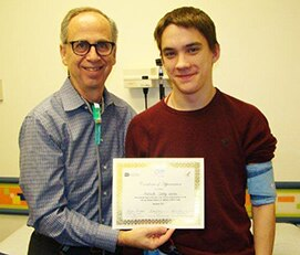 Photo of Dr. Bradley Warady and Malachi Gerke holding certificate marking their tenth year of participation in Chronic Kidney Disease in Children study
