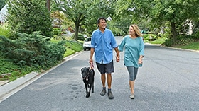 Photo of man and woman walking with dog