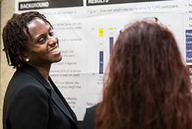 Attendees of the 2016 meeting of the Network of Minority Health Research Investigators talk at a poster session.