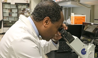Photo of Dr. Griffin P. Rodgers looking through a microscope