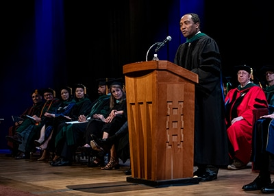 Photo of : Dr. Griffin P. Rodgers delivering the keynote address at George Washington University's 2018 M.D. Diploma Ceremony.