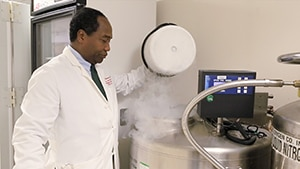 Photo of Dr. Griffin P. Rodgers in labcoat observing liquid nitrogen tank.