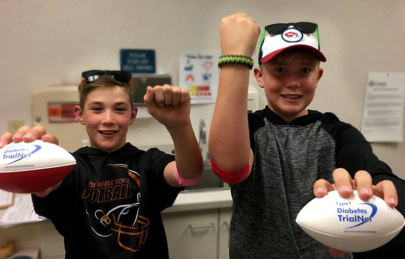 Two brothers hold Type 1 Diabetes TrialNet labeled footballs.