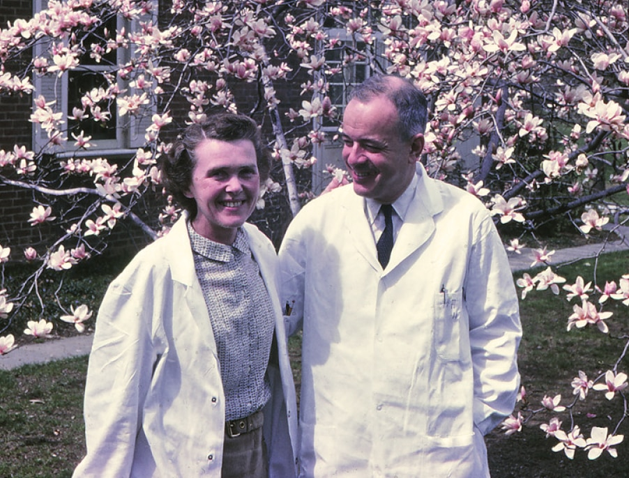 Herbert Tabor and Celia in lab coat in front of a blooming tree.