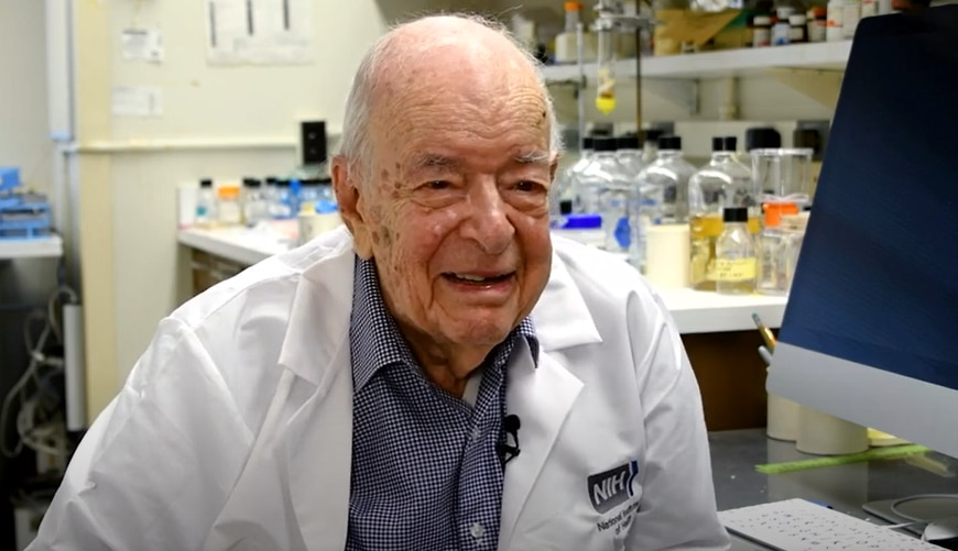 Dr. Herbert Tabor being interviewed in a lab.