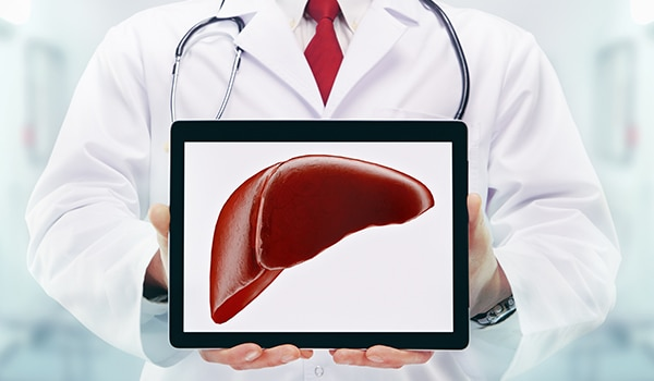 A doctor holding an iPad with an image of a liver.