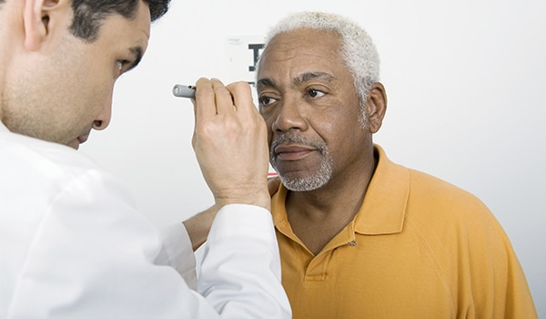 Male doctor giving male patient eye exam