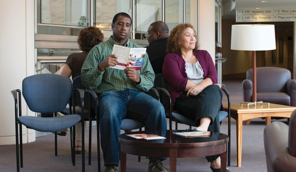 Image of a young man and a middle-aged woman sitting in a waiting room. The man is reading a pamphlet and the woman has her legs crossed and looking up.
