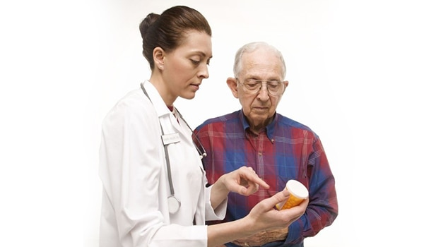 Physician discussing medication label with patient in a one on one setting.