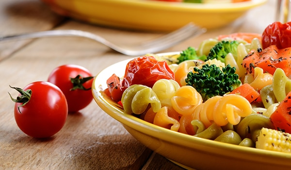 A bowl of pasta with vegetables.