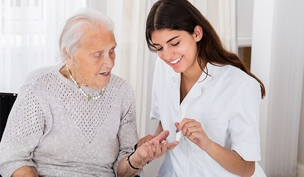 A health care professional helping an elderly woman check her blood glucose level.