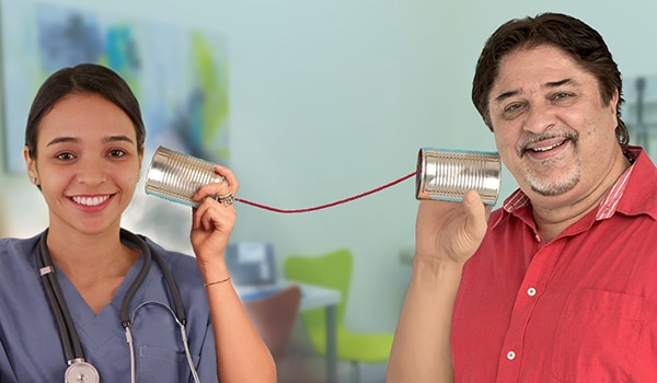 Photo depicting the telephone game with woman holding can next to her ear with string connected to another can that man is holding next to his ear.