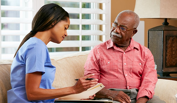Image of a young female doctor sitting on a couch looking over paperwork with an older male patient.