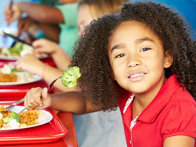 A child with a plate of healthy food at a school cafeteria