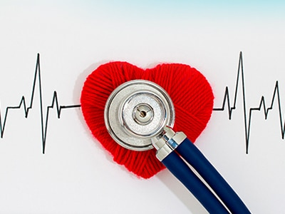 Stethoscope overlaid on a red heart made from yarn and a picture of an EKG