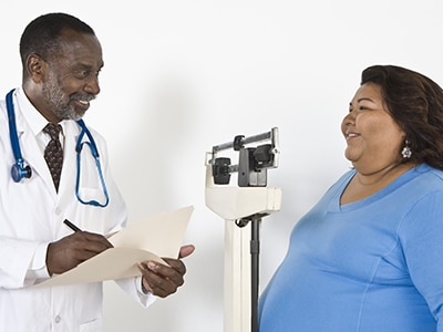 Doctor with a woman stepping on a scale