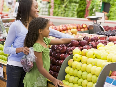 Mother and young daughter shopping for fruit
