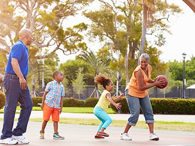 Grandparents and grandchildren playing basketball