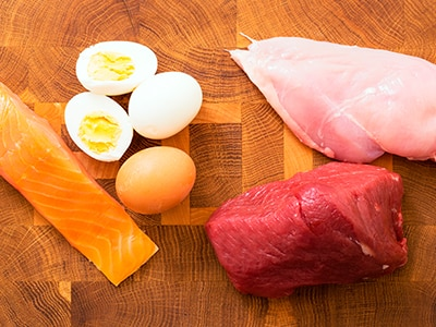 Hard-boiled eggs and pieces of uncooked salmon, chicken, and beef