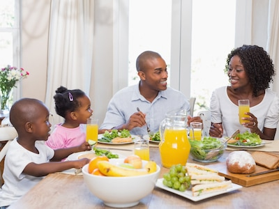 An African-American family eating a healthy meal.