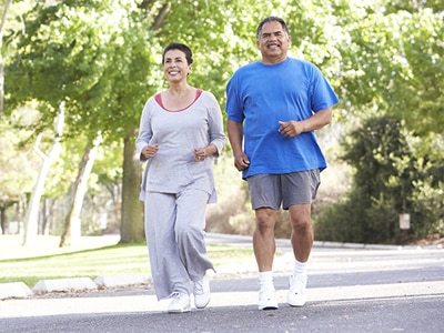 An older Hispanic couple out for a jog.