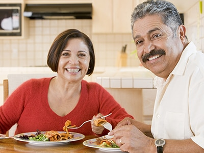 Man and woman eating pasta and salad at a kitchen table
