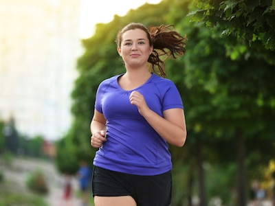 An overweight young woman smiling and jogging