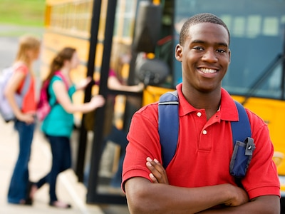 Teenager smiling in front of a school bus