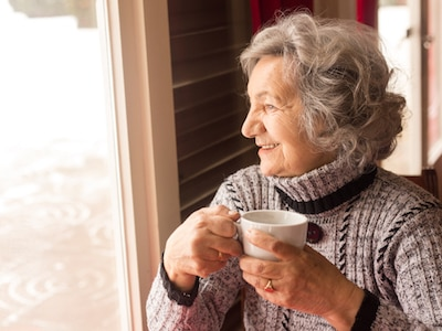 Older woman drinking coffee and looking out of a window