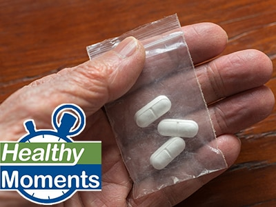 Hand holding small plastic bag containing three pills