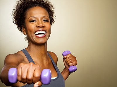 Smiling woman working out with a set of purple hand weights