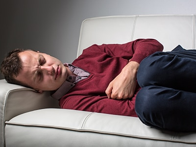 Man lying on a couch with his knees bent and his arms folded across his stomach