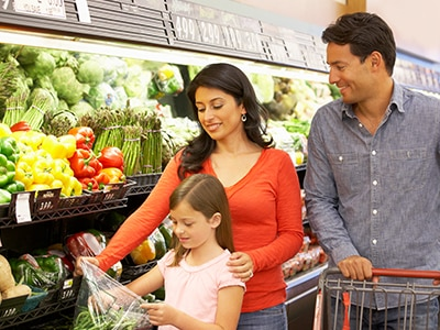 Parents and child shopping for produce at a grocery store