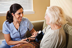 A nurse takes the blood pressure of an elderly lady
