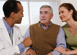 Older man with a younger woman talking to a doctor