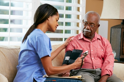 Man having his blood pressure checked by a health care professional.