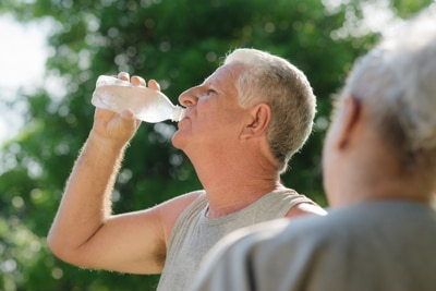 Photo of a man outdoors in exercise clothes drinking from a bottle of water.