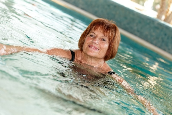 Photo of a smiling middle-aged woman in a swimming pool