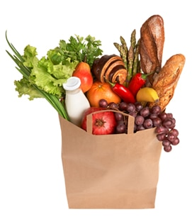 Photo of a bag of groceries containing fruit, vegetables, milk, and bread.