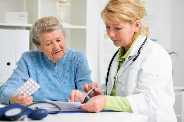 Photo of an older woman talking with her doctor. They are looking at a piece of paper.