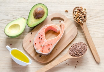 Photo of avocado, salmon, nuts, seeds, and olive oil.