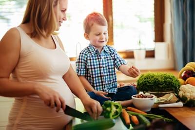 Eine schwangere Frau, die Gemüse in der Küche mit ihrem jungen Sohn hackt.