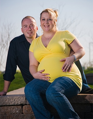 A pregnant woman sitting outdoors with her husband behind her.
