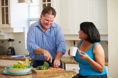A man chopping vegetables in the kitchen and a woman sitting on a stool talking with him.