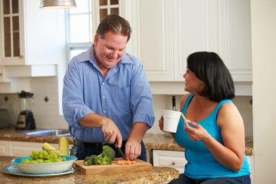 Ein Mann, der Gemüse in der Küche hackt und eine Frau, die auf einem Schemel sitzt, der mit ihm spricht.